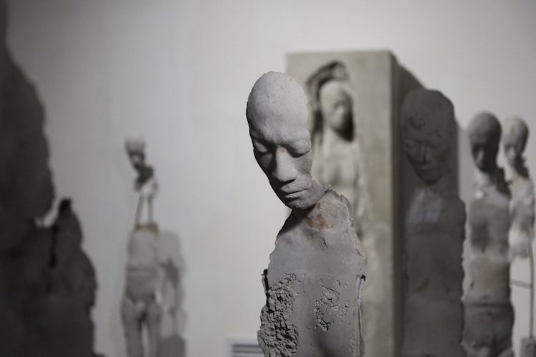 Life sized sculptures of fractured figures contemplate
