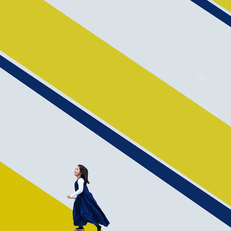 Woman in blue and White walking along a yellow, blue, and white wall.