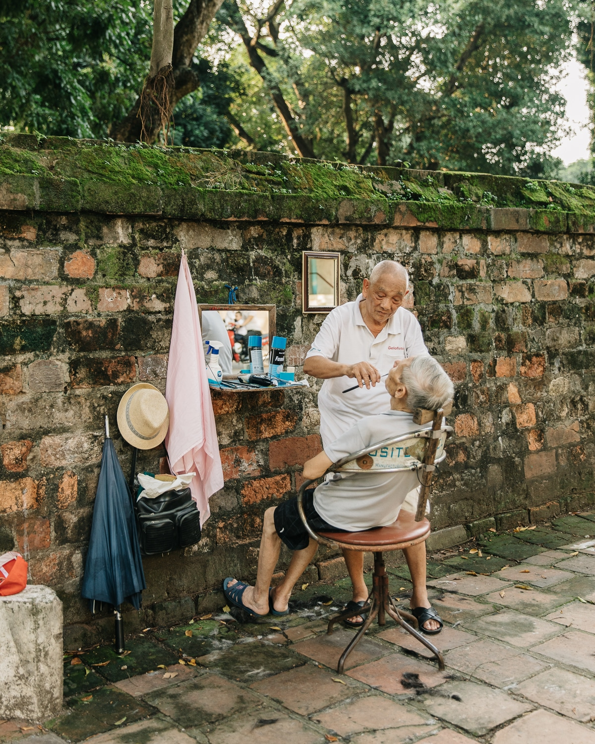 A barber at work next to the walls of the Temple of Literature in Hanoi