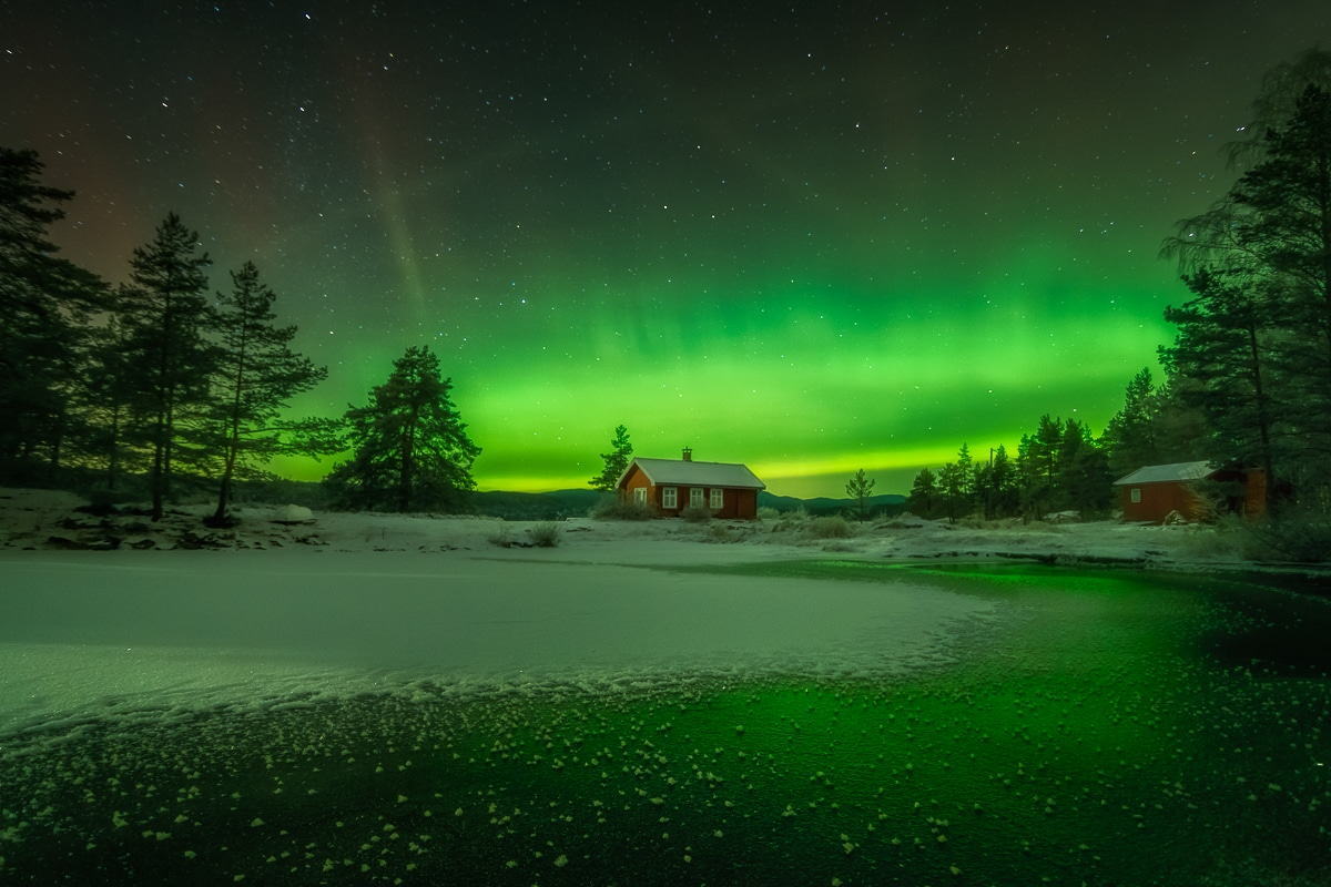 Red Cabin Under the Aurora Borealis
