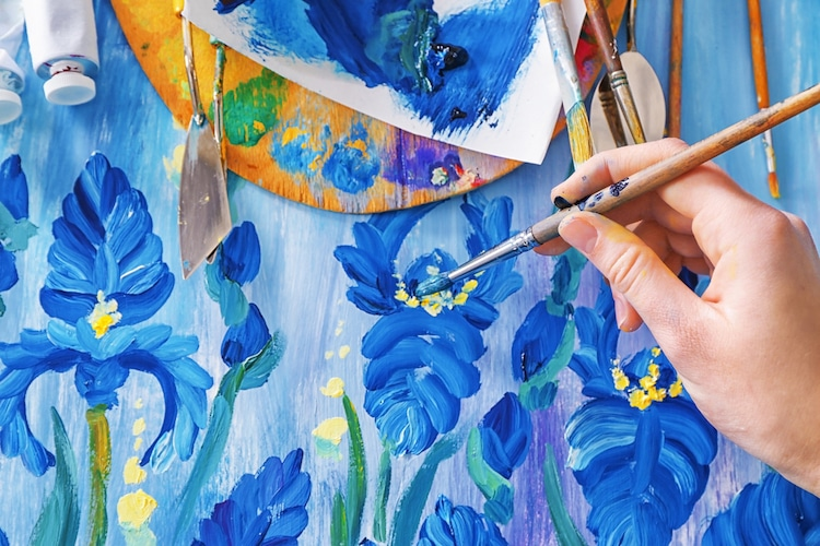 A person that is painting blue flowers
