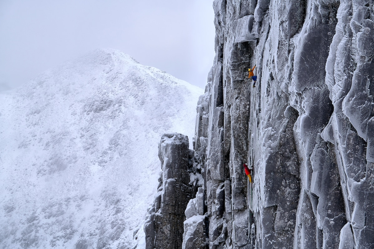 Two Rock Climbers Scaling a Mountain