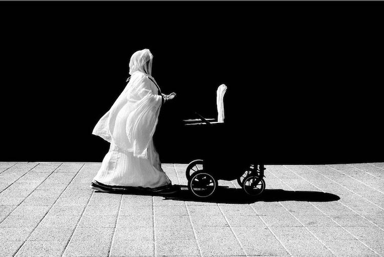 Black and White Photo of a Woman Pushing a Stroller by Alan Schaller