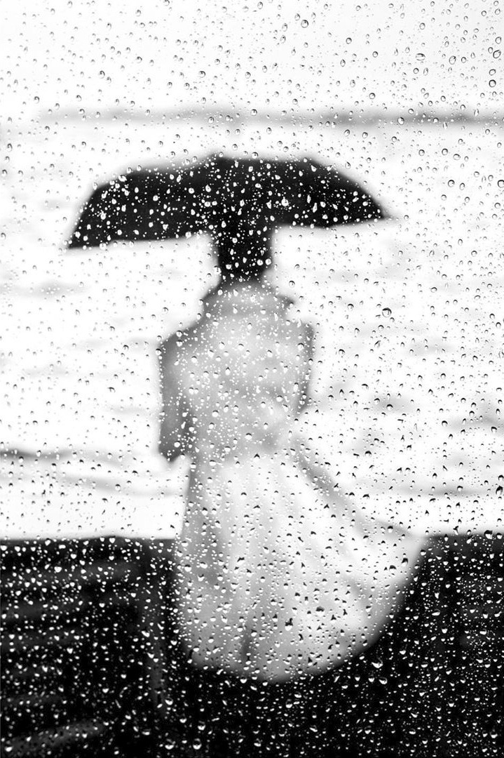 Black and White Photo of Person Under an Umbrella