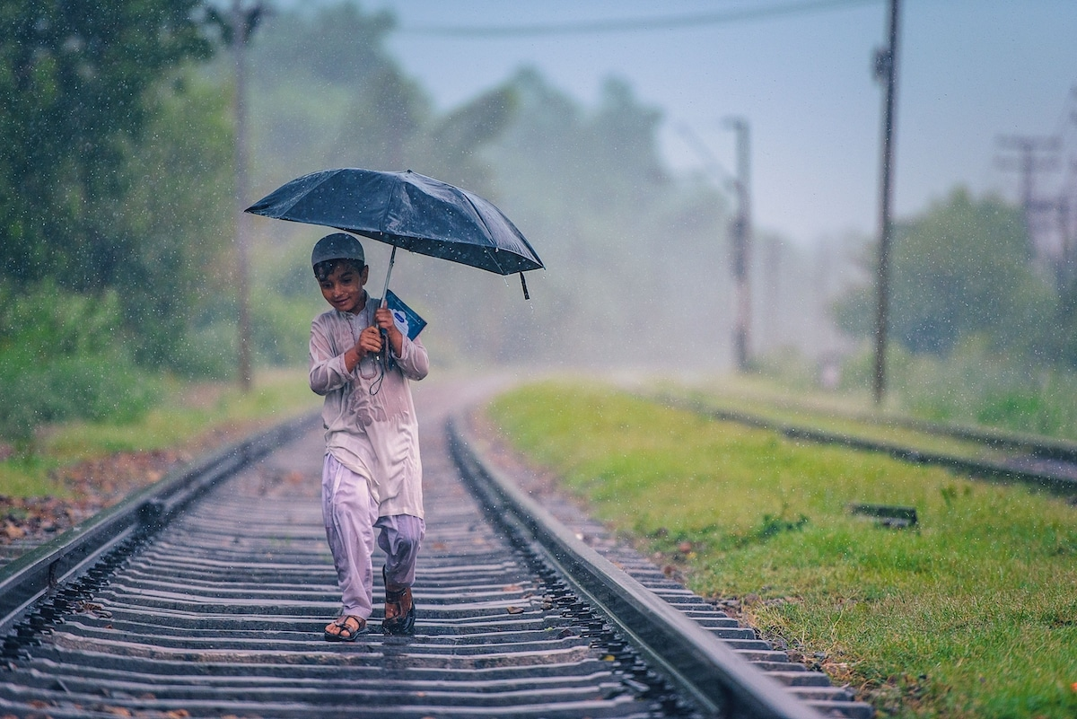 Boy Walking on Train Tracks in the Rain