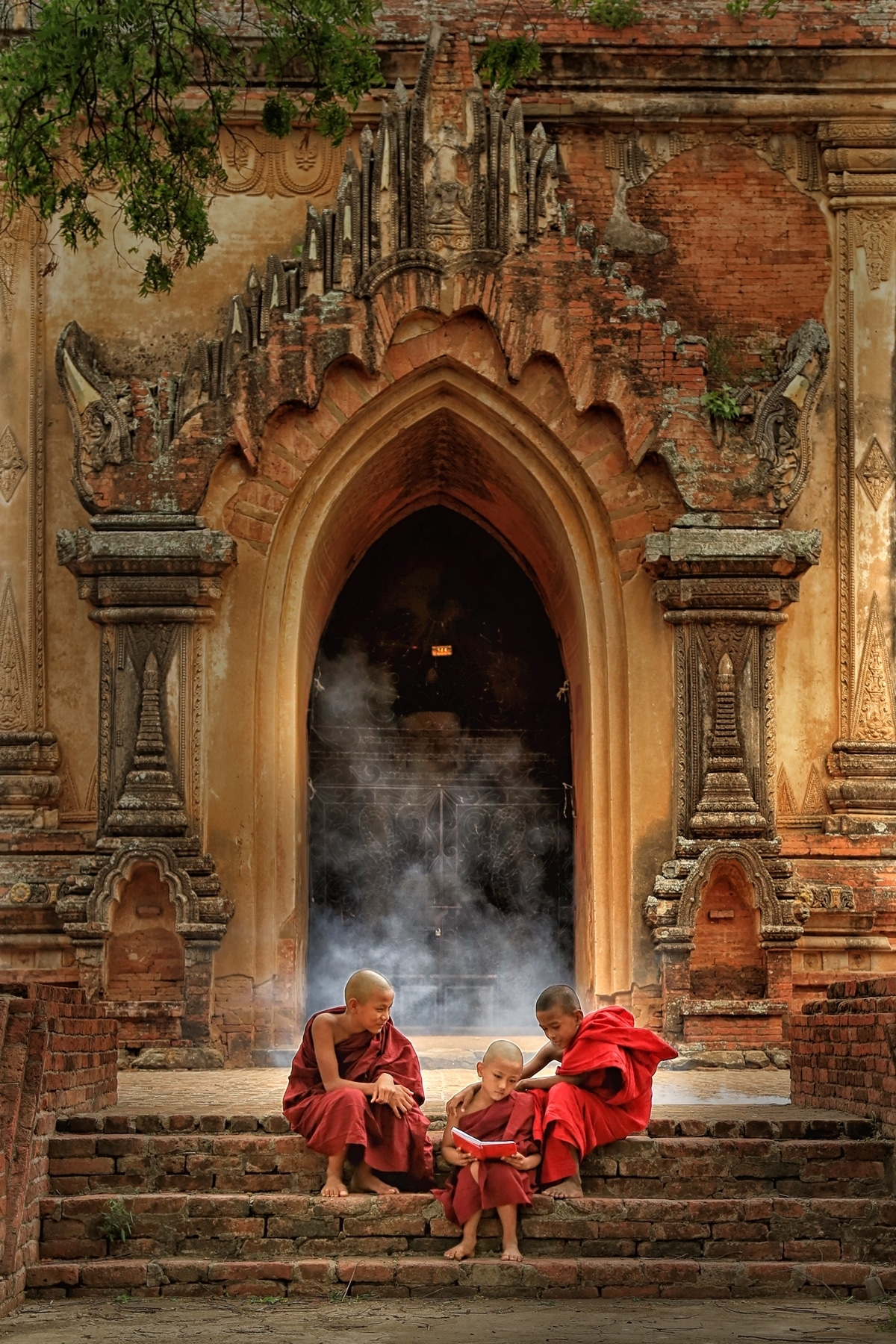 Young monks reading while sitting on the steps of an ancient building