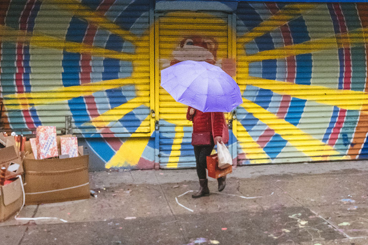 Person Holding a Purple Umbrella with Sun Mural in Background