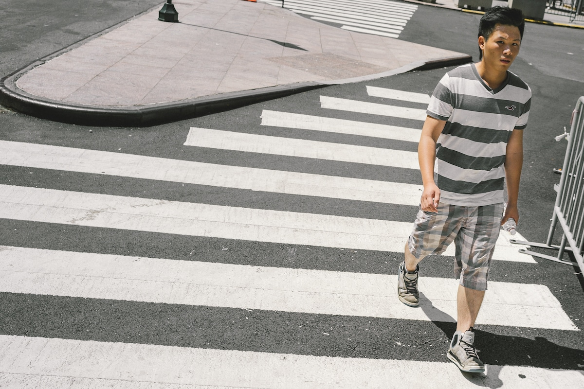 Man Crossing the Street in a Striped Shirt