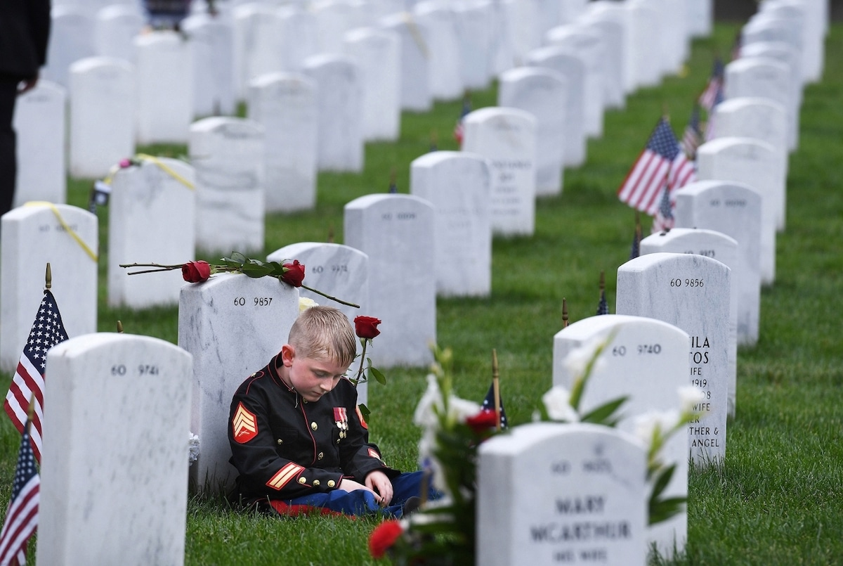 Niño sentando junto a una lápida