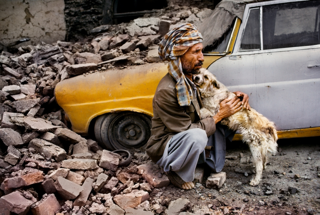 Man holds a dog in front of a car in Kabul by Steve McCurry