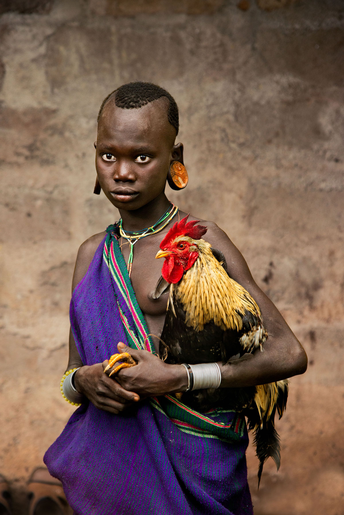 A girl of the Kara tribe holds a rooster by Steve McCurry