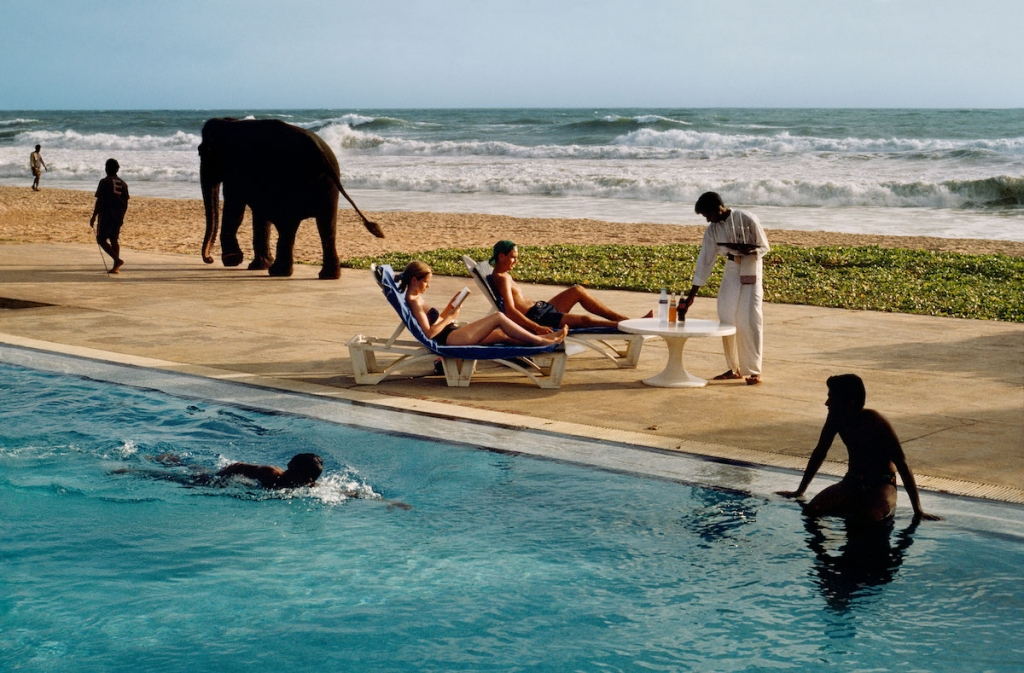 Tourists lounge poolside as elephant passes in Sri Lanka by Steve McCurry