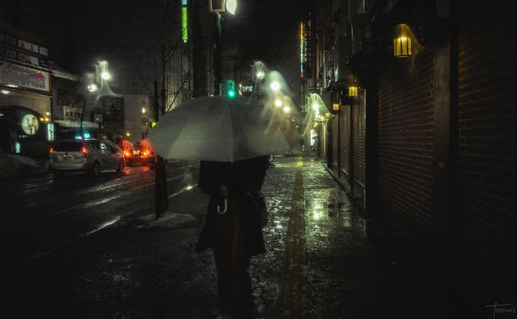 Person with Umbrella Walking Down Dark Street in Japan