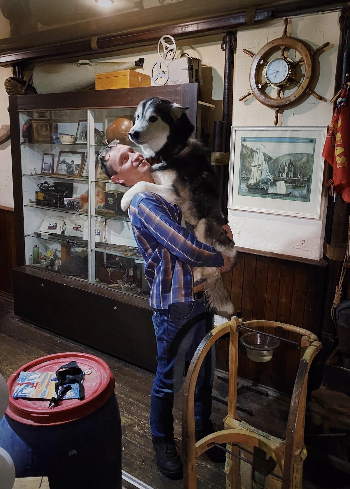 Man Holding Husky in Murmansk Russia