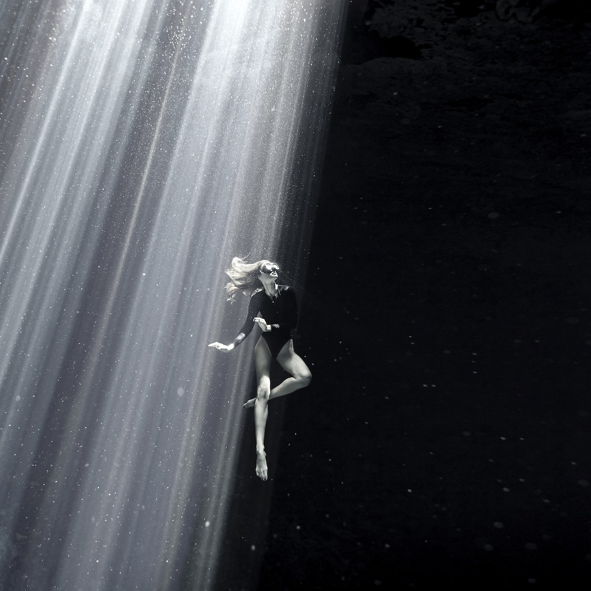 Woman Underwater With Rays of Sun Shining Down