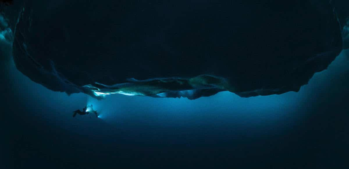 Diver Shines Light on Iceberg Underwater