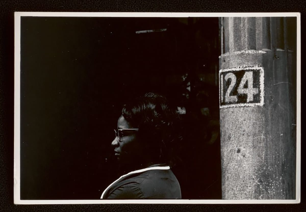 african american woman sitting beside a pole labeled 124