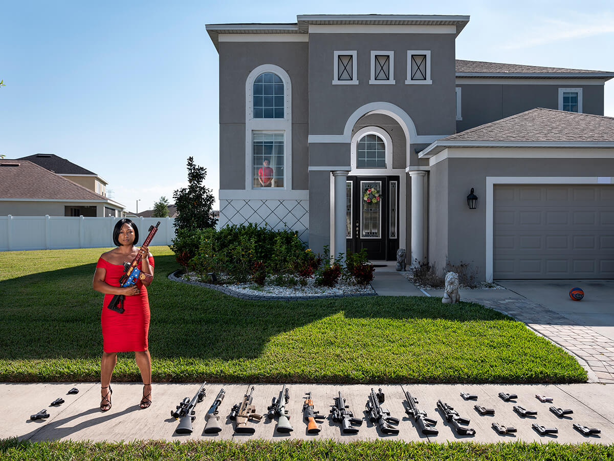 Woman Posing Outside of Her House with Her Guns