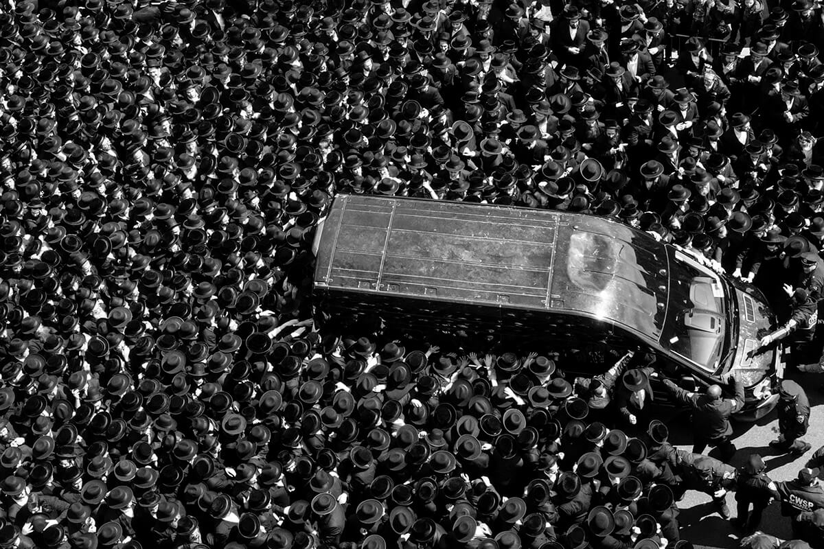 Black and White Photo of Van Swarmed By People in a Crowd