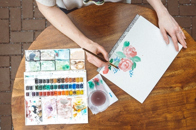 Overhead view of woman at a table painting with watercolors