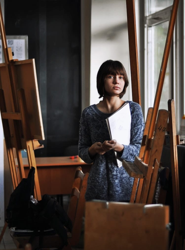 Artist Standing Among Easels