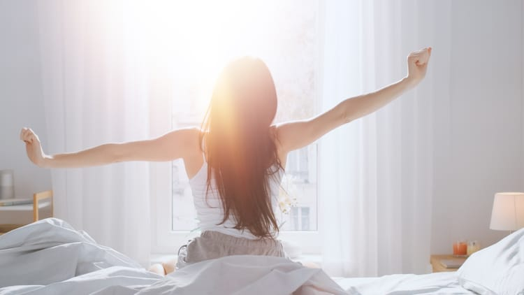 Woman Stretching Her Arms in Bed