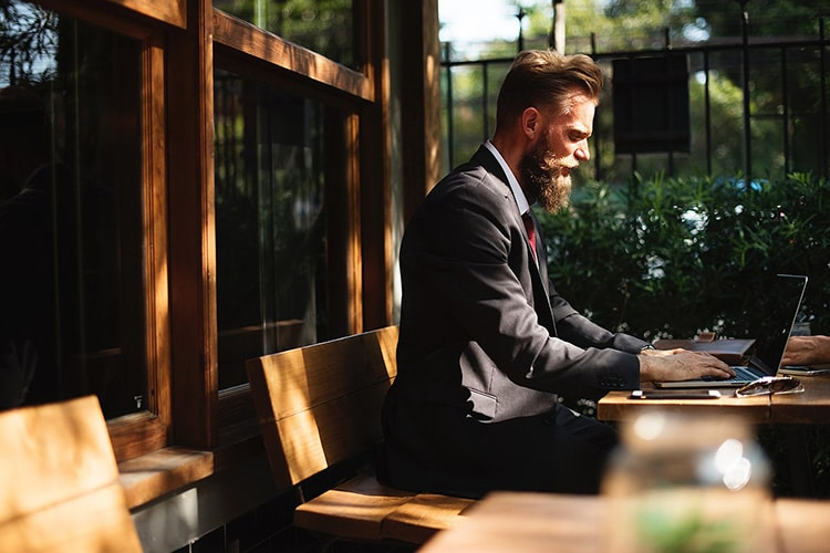 a bearded man in a suit works outside on his laptop surrounded by green flora