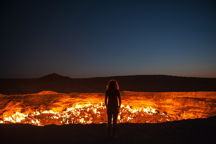 Women Facing Darvaza Crater in Turkmenistan at Night