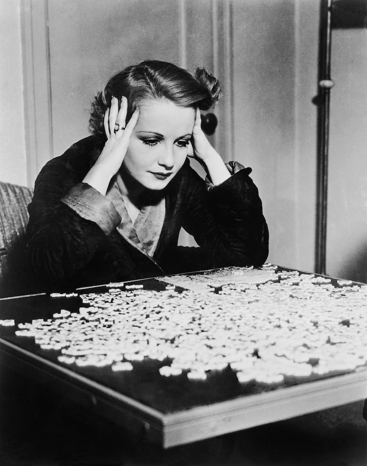Black and White Photograph of Someone Solving a Puzzle