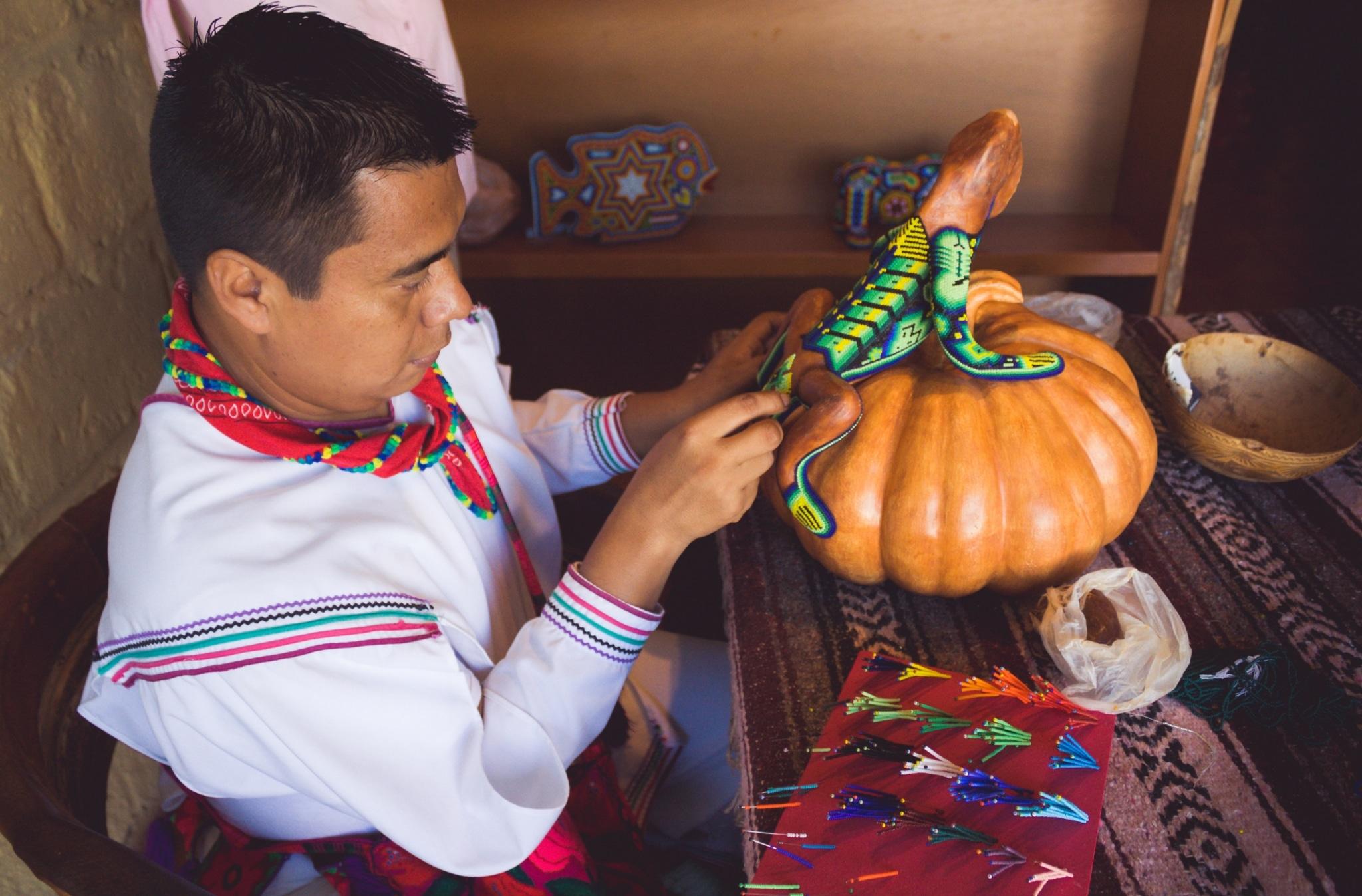 Artesano huichol trabajando en una pieza de chaquira