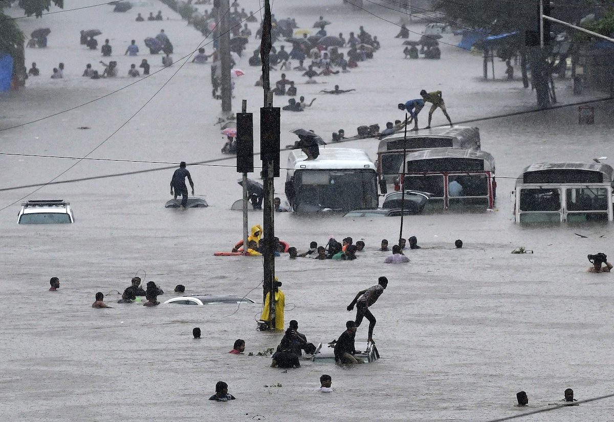 People Walking on Cars Submerged in a Flood in Mumbai