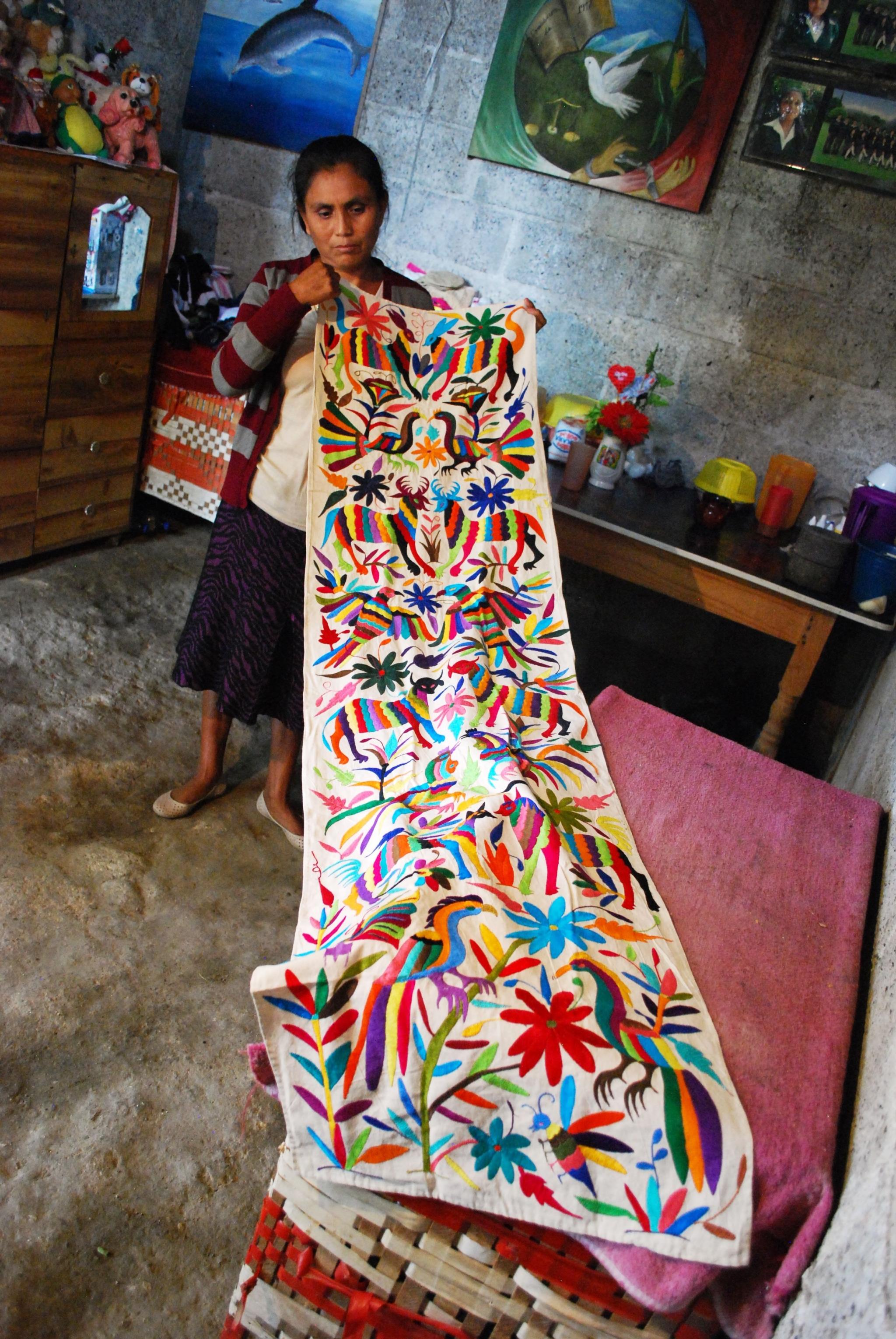 Artesana sosteniendo un tenango bordado