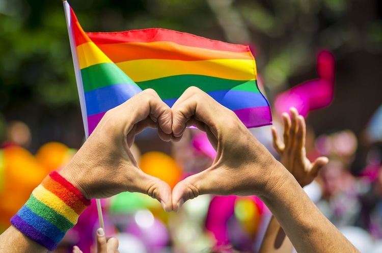 Heart Sign Formed with Hands with Gay Pride Flags in the Background