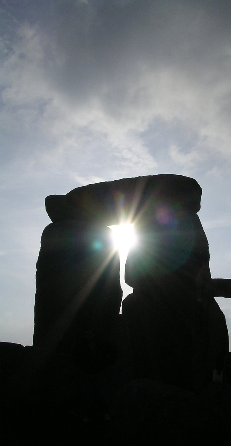 The sun peeks through Stonehenge's Trilithons