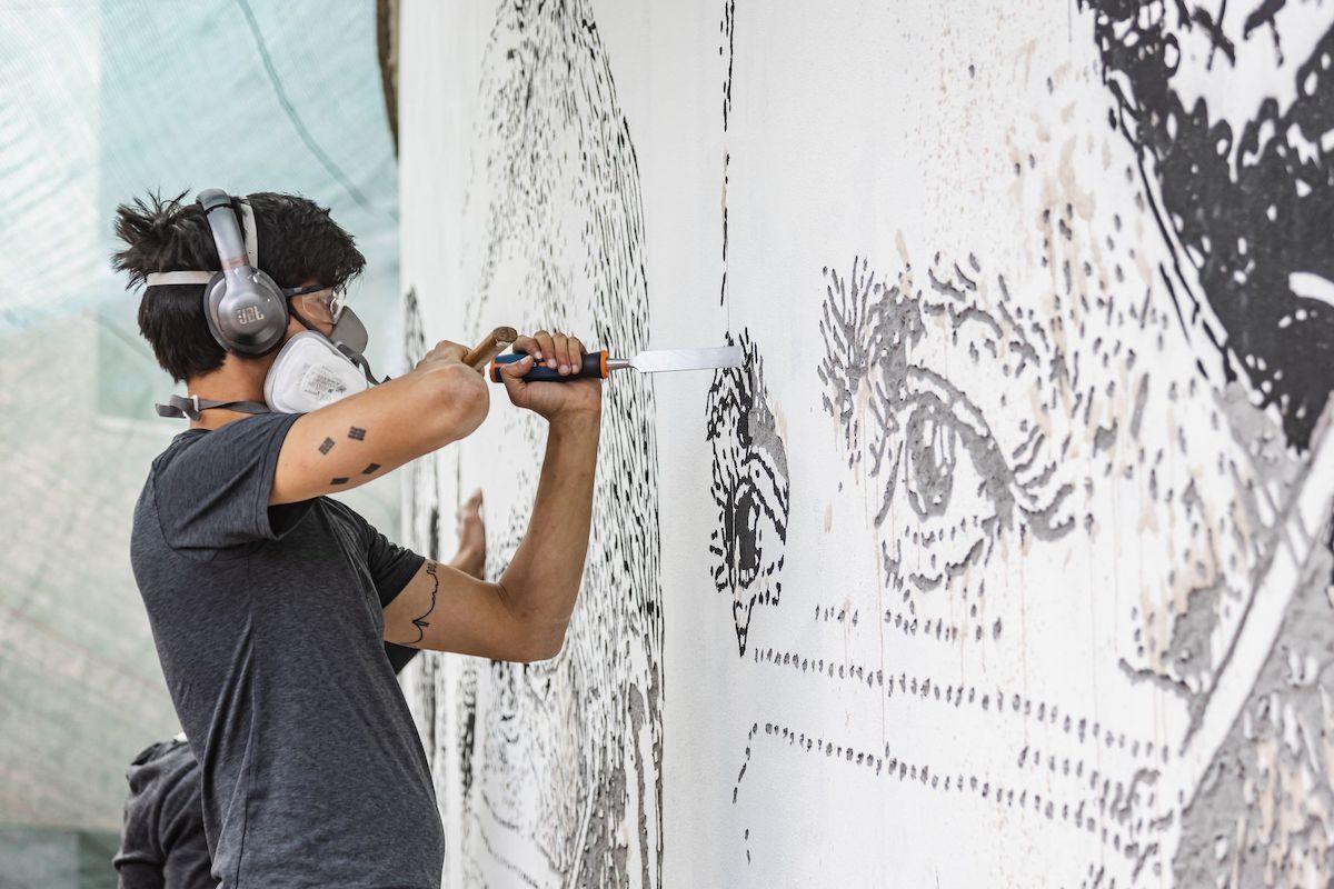 El artista callejero Vhils trabajando en un mural en un hospital de Oporto