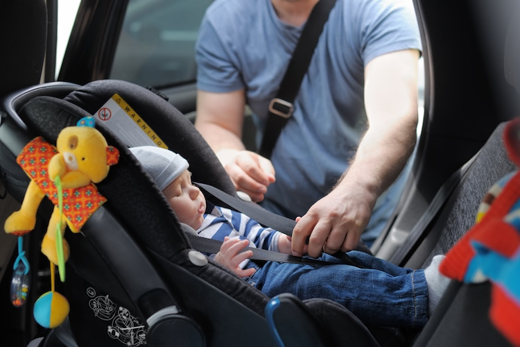 Baby Being Strapped Into a Car Seat