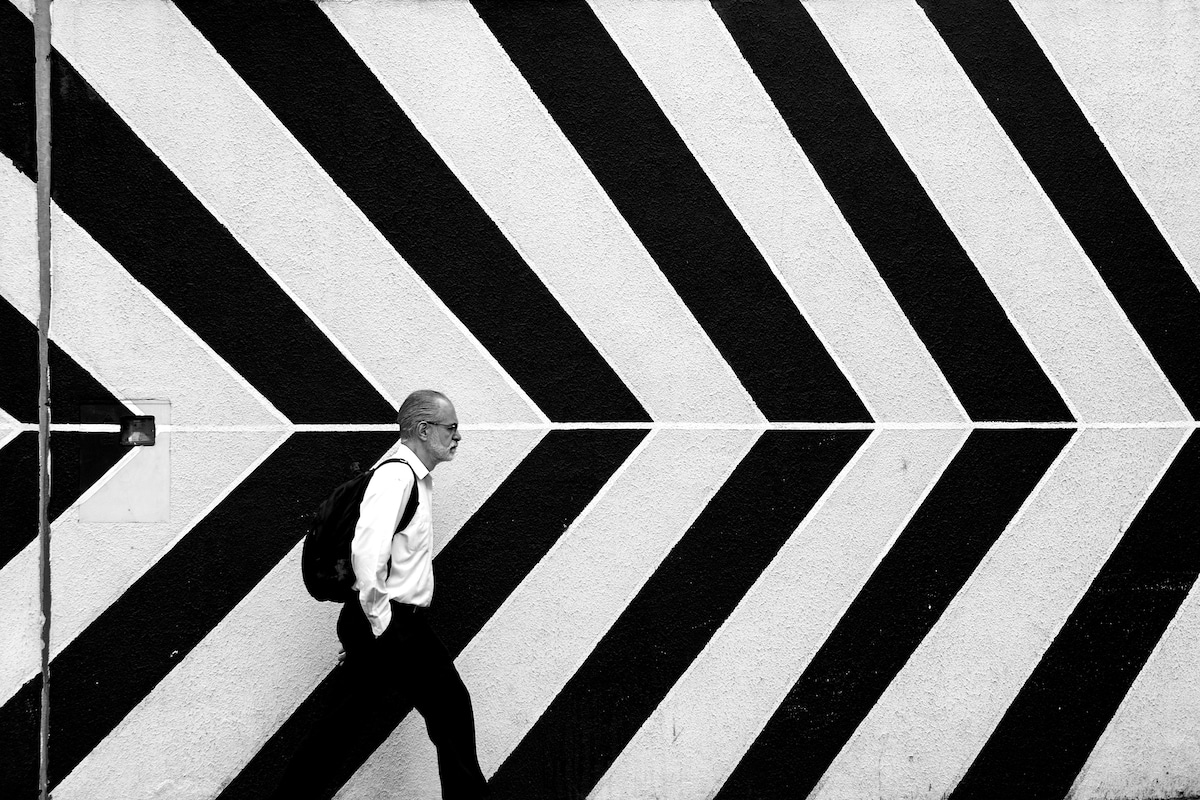 Man Walking past a stripped background