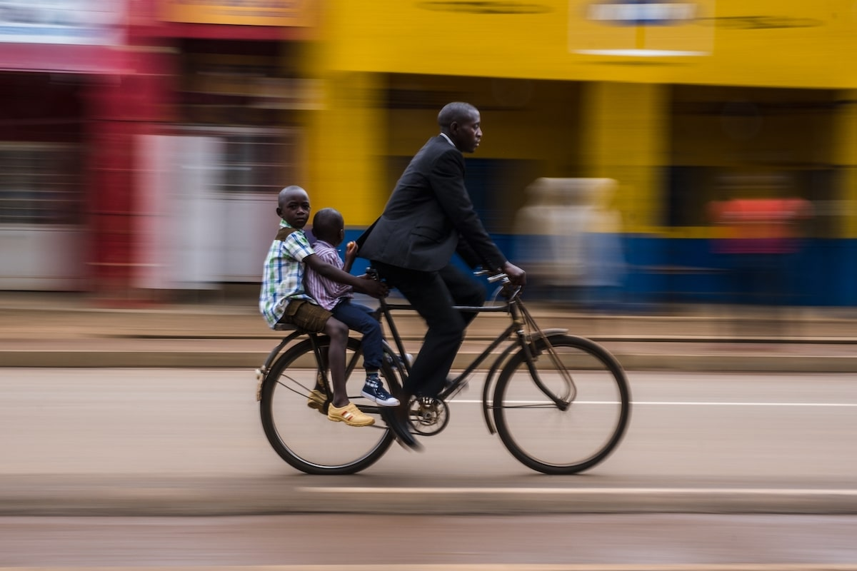 Man Biking with His Children on the Back in Rwanda