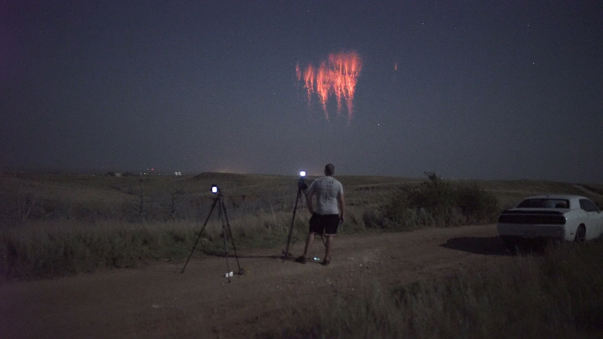 Man with Camera Equipment Photographing a Red Sprite