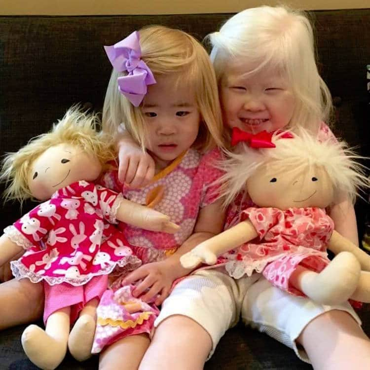 Two Girls Cuddling With Dolls That Look Like Them