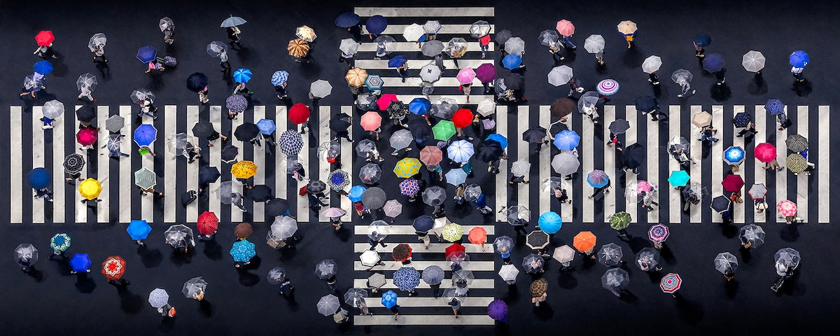 Aerial Photo of Pedestrians with Umbrella Crossing the Street