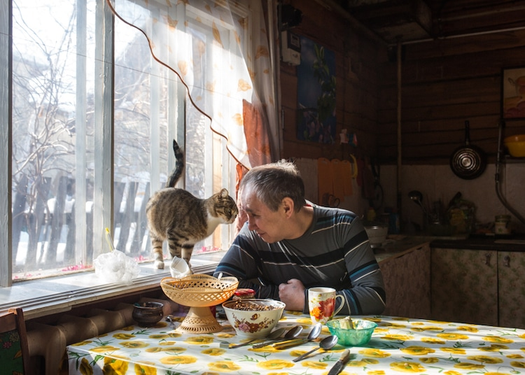 Man Sitting at the Kitchen Table with His Cat