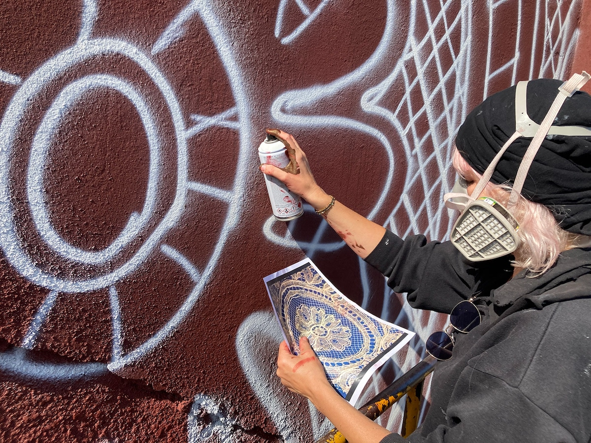 Female Street Artist Nespoon Using Spaypaint to Create Mural in Calais