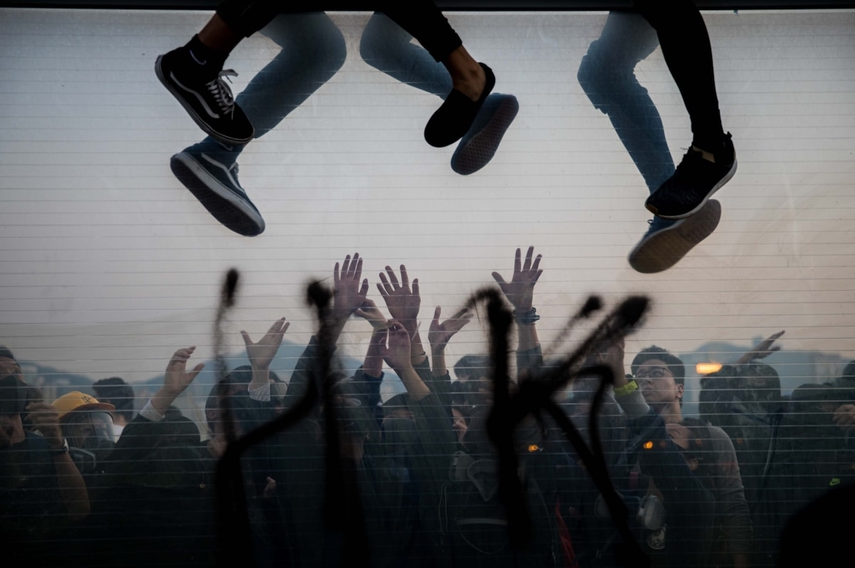 Protestors in Hong Kong Climbing Over a Barricade