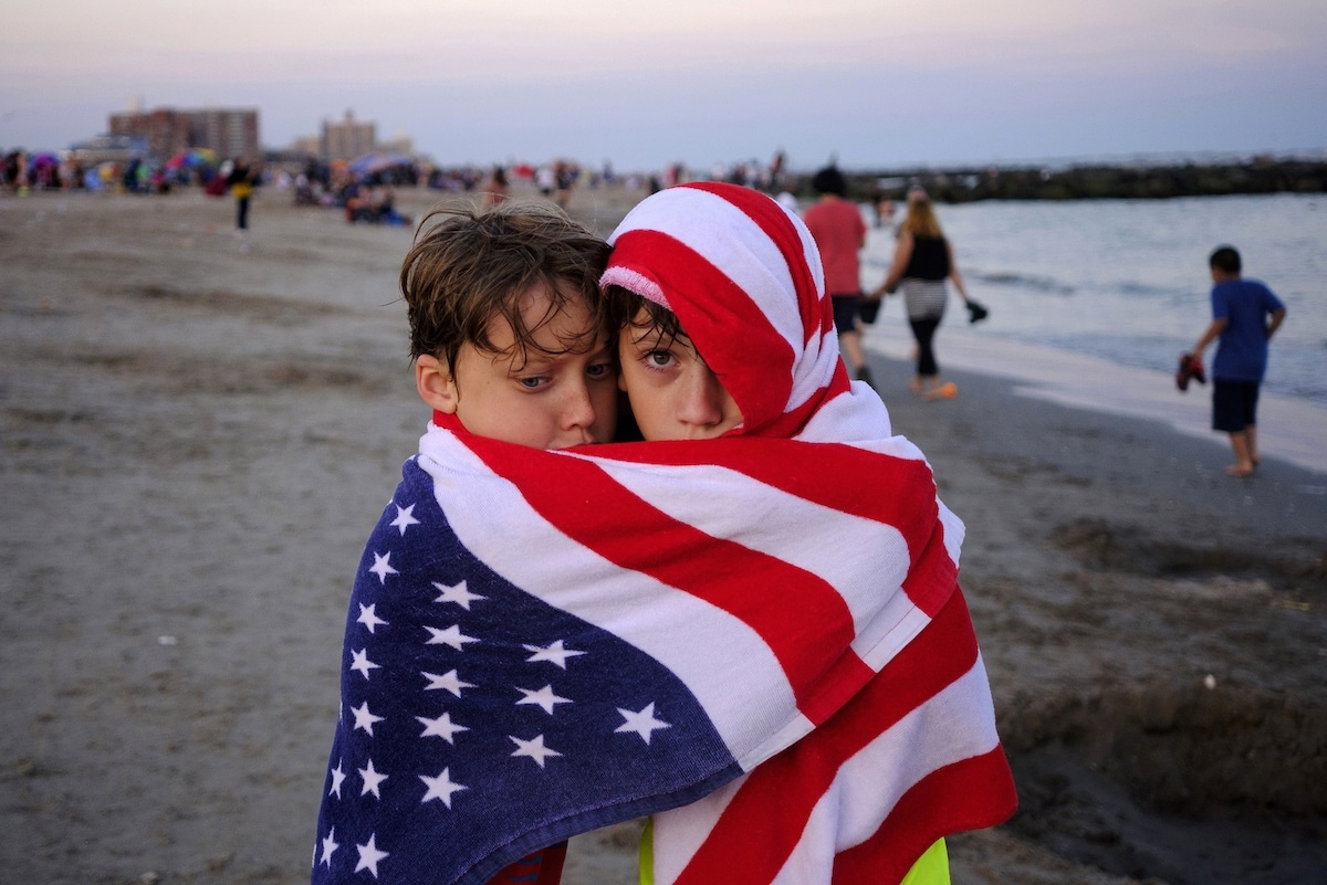 Portrait of Two Children on the Beach Wrapped in an American Flag