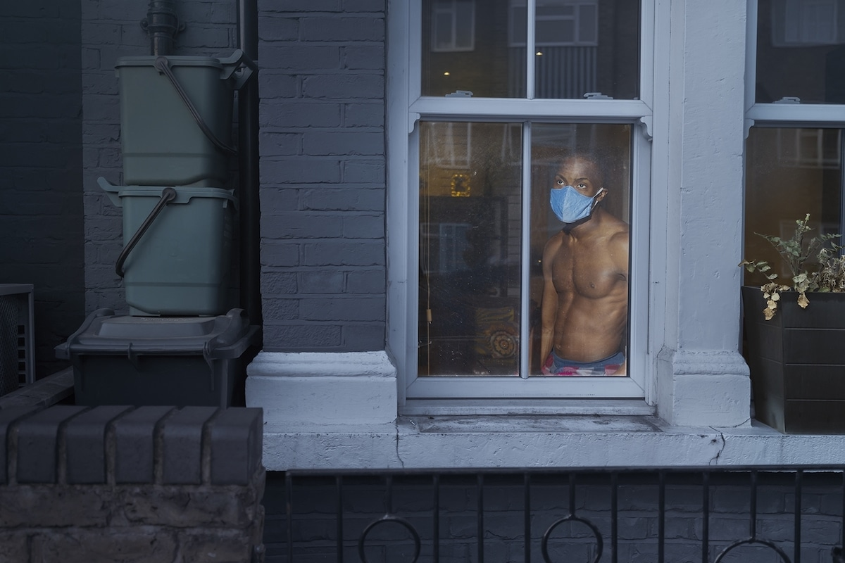 Man with Face Mask Looking Out the Window