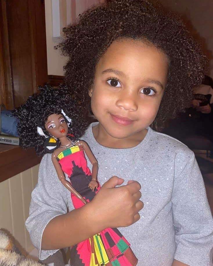 Girl Holding Diversity Doll by Ymma