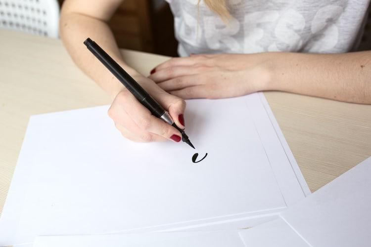 Une personne qui dessine avec un stylo-pinceau