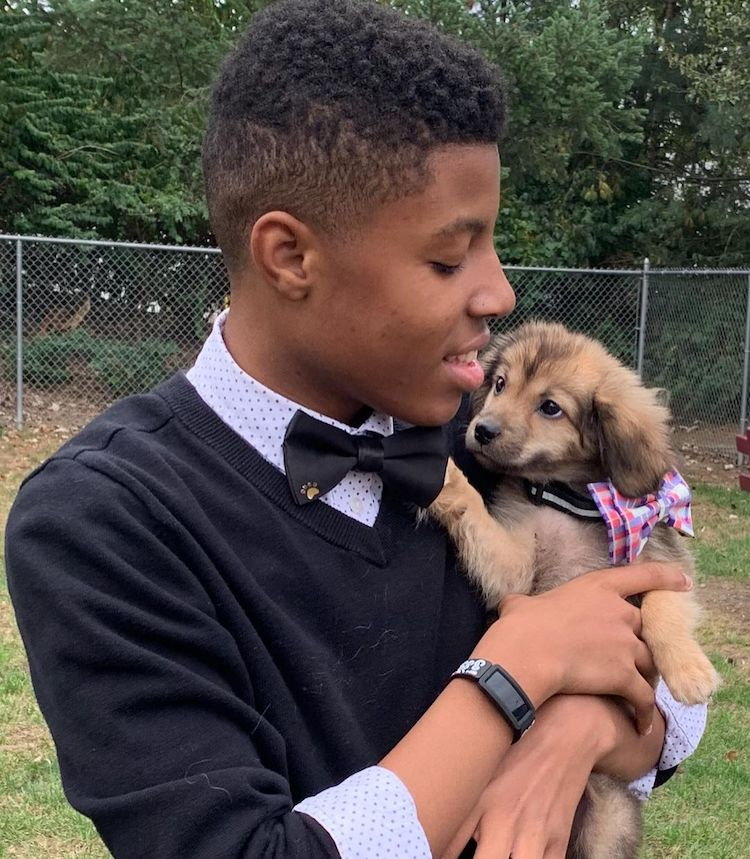 Sir Darius Brown Holding a Puppy Wearing a Bow Tie