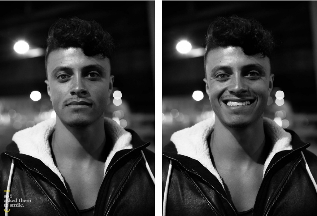 A young man stares, then smiles, at the camera in a black and white image